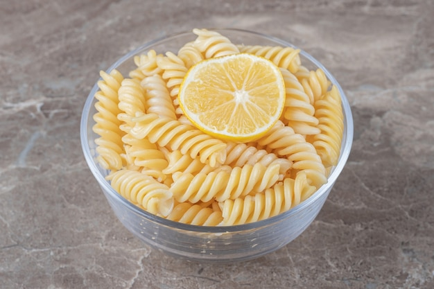 A slice of lemon in the fusilli pasta on the bowl , on the marble surface.