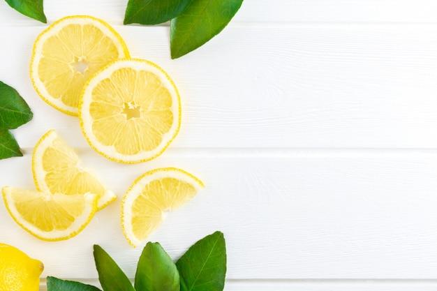 Slice of lemon and green leaves background