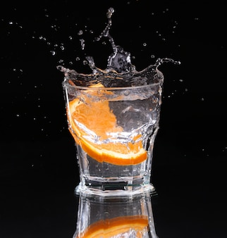 Slice of lemon splashing into a glass of water with a spray of water droplets in motion suspended in the air above the glass
