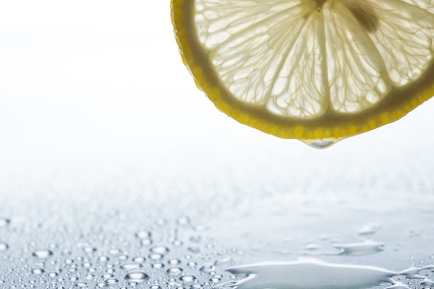Slice of lemon on a steel reflective  with water drops