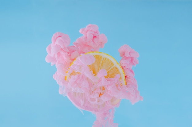 Slice lemon with partial focus of dissolving pink poster color in water on blue background.