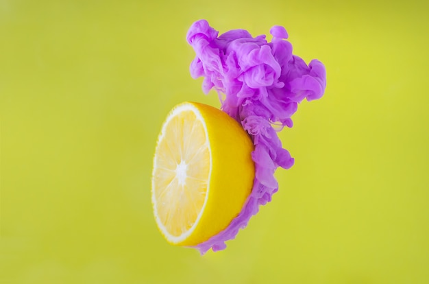 Slice lemon with partial focus of dissolving violet poster color in water on yellow background.