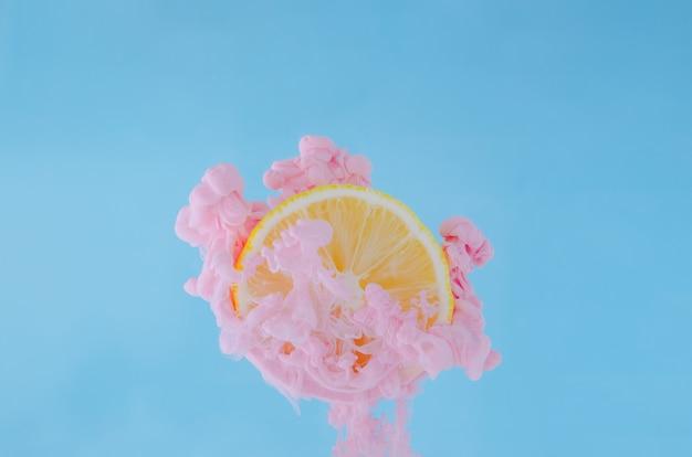 파란색 배경에 물에 분홍색 포스터 색상을 녹이는 부분 초점 레몬 슬라이스.