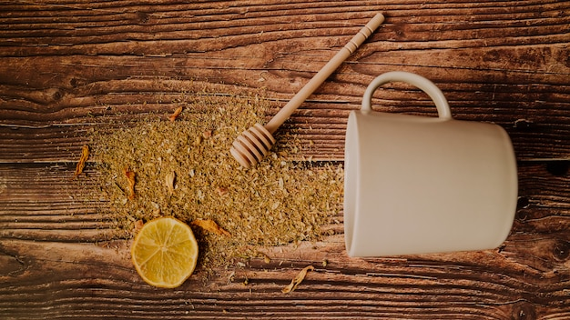 Slice of lemon with spilled tea herbs top view