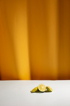 Slice of limes on white table in front of yellow curtain