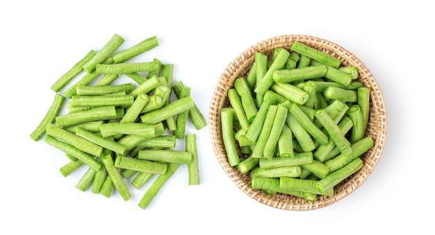 白い表面に隔離されたバスケットに長い豆をスライスします。上面図