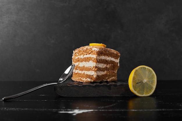 Una fetta di torta medovic servita con il limone.