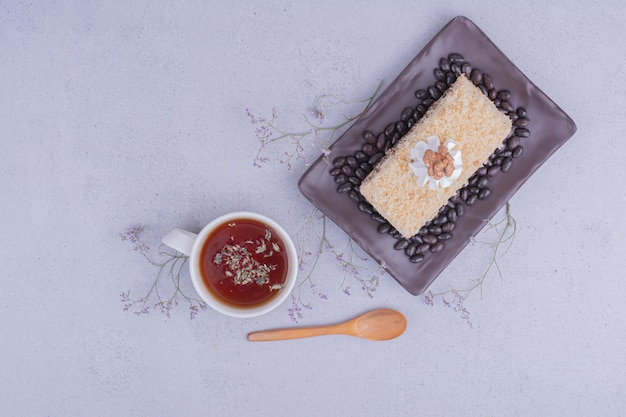 A slice of medovic cake with chocolate beans in a black platter with a cup of tea