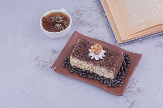 A slice of medovic cake with chopped chocolate in a platter