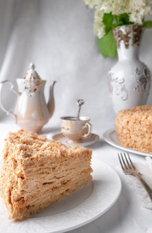 Slice of multilayer napoleon cake with butter cream on a white plate closeup there is a napkin and a fork near a plate in the background is a cup teapot and a vase of flowers grey background