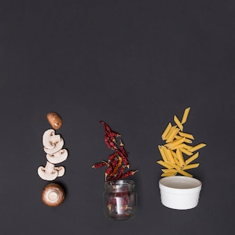 Slice of mushroom; dried red chili and penne raw pasta over black slate background