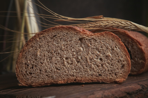 まな板と暗い茶色のクローズアップでパンのスライス