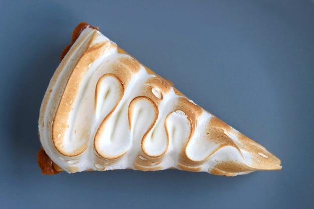 Кусочек вкусного лимонного пирога безе на сине-серой тарелке