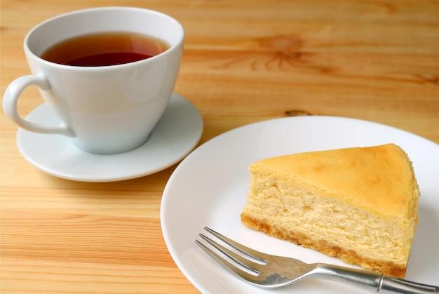 나무 테이블에 제공되는 뜨거운 차 한잔과 함께 구운 치즈 케이크 조각