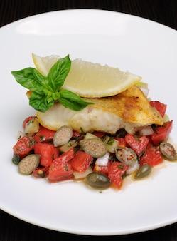 Кусочек запеченного рыбного окуня с овощным гарниром и лимоном