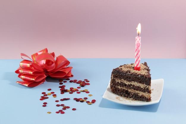 파란색 배경에 촛불과 색종이 조각이 있는 생일 케이크 조각