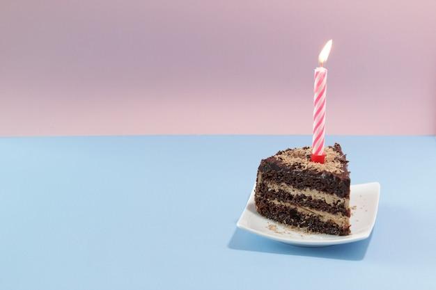 파란색 배경에 촛불이 있는 생일 케이크 한 조각