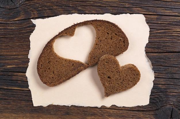 Кусочек черного хлеба с вырезом в форме сердца на рваной бумаге