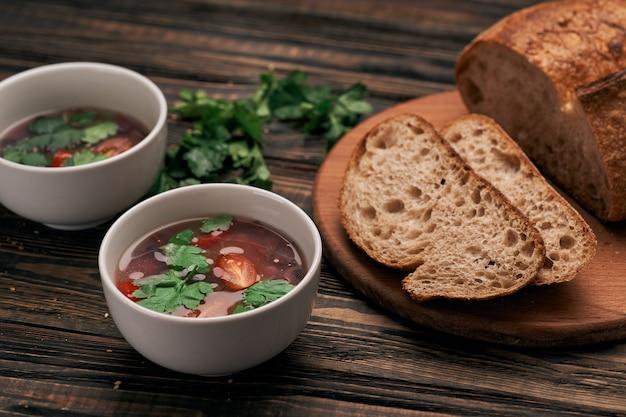 Кусок хлеба и две тарелки супа на деревянной доске