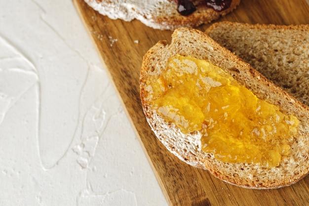木の板にフルーツジャムで覆われたパンのスライス