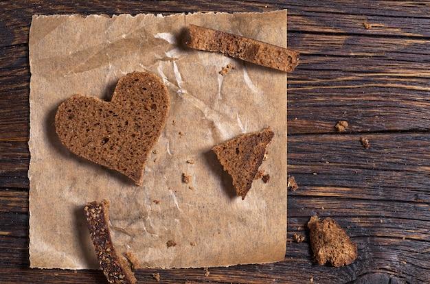 Ломтик хлеба в форме сердца на мятой бумаге на старом деревянном столе
