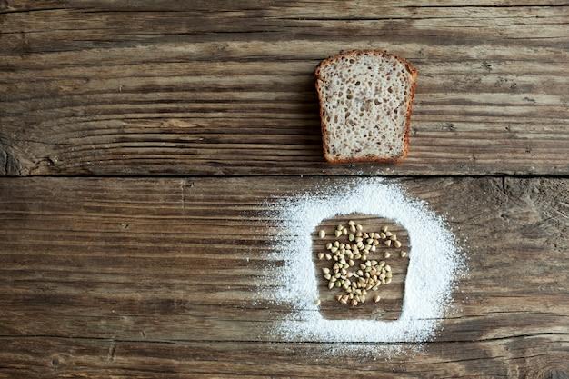 有機緑そばから作られたパンのスライスは、シリアルと小麦粉の隣にある古い木製のテーブルの上にあります