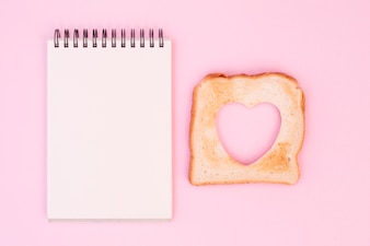 Slice of bread with cut out heart and notepad