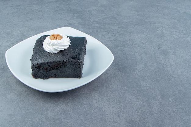 하얀 접시에 브라우니 케이크 한 조각.