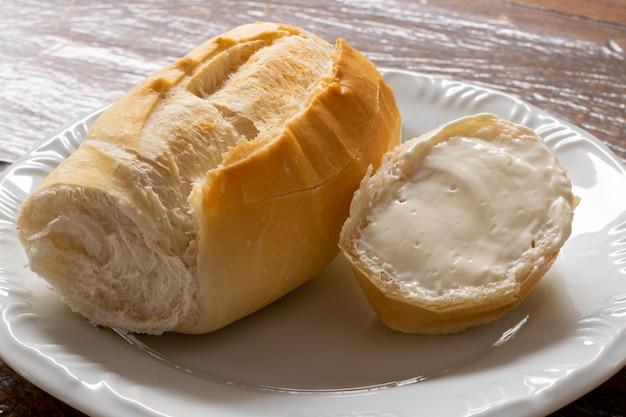バターを塗った塩パンのスライス。皿の上のフランスのパン。