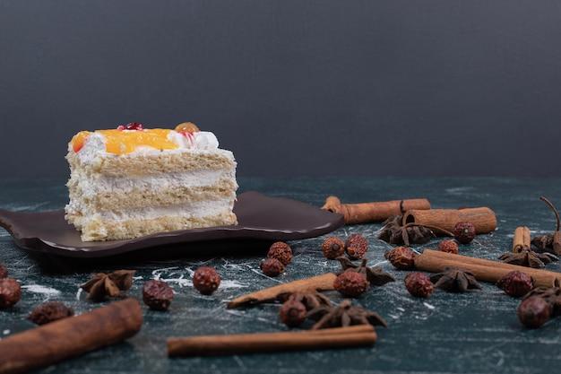 大理石のテーブルにケーキ、シナモン、コーヒー豆のスライス。高品質の写真