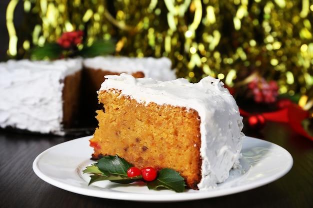 木製のテーブルと明るい背景にクリスマスの装飾とケーキで覆われたクリームのスライス