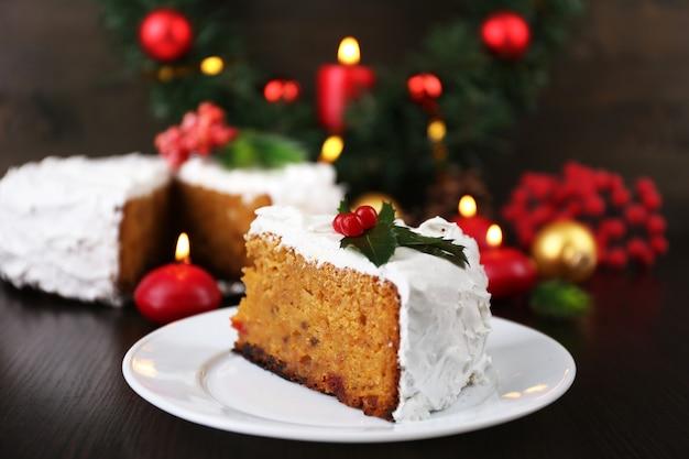 木製のテーブルの背景にクリスマスの装飾とケーキで覆われたクリームのスライス