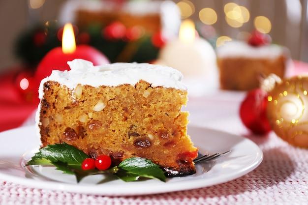 밝은 배경에 크리스마스 장식이 있는 테이블에 케이크 조각