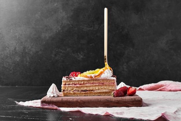 Кусочек торта с ягодами на деревянном блюде.