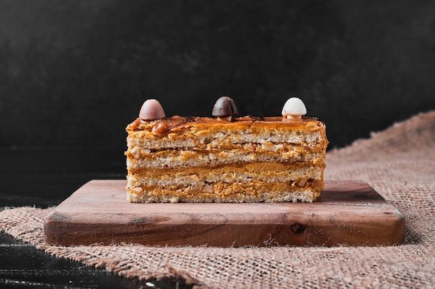 나무 접시에 카라멜 케이크의 조각입니다.
