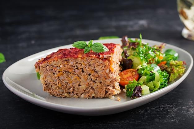 Кусочек запеканки с рисом, фаршем из говядины и капустой с томатным соусом сверху, украшенный базиликом на тарелке