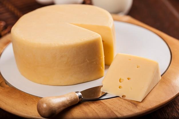木製のテーブルにナイフでチーズのスライス。