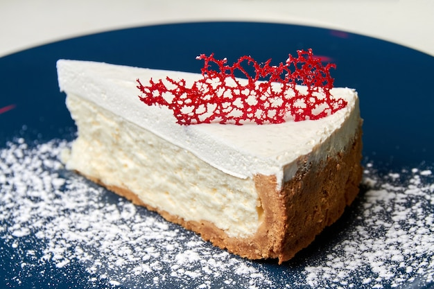 Кусочек чизкейка на синей тарелке с карамельным декором