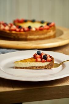 プレート上のチーズケーキのスライス。木製の背景