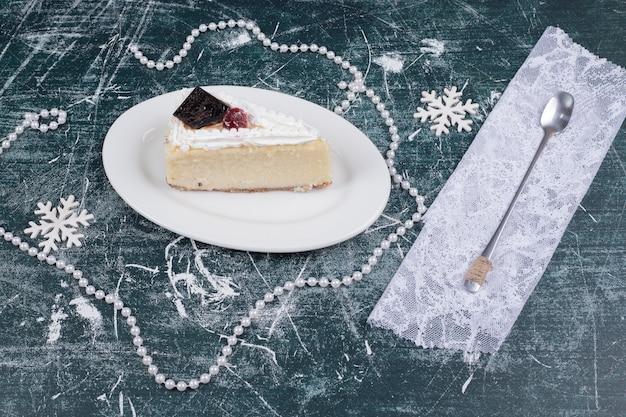 Кусочек чизкейка на белой тарелке с ложкой и жемчугом. фото высокого качества