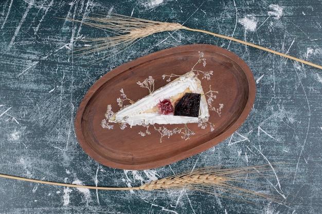 Кусочек чизкейка на деревянной тарелке с пшеницей. фото высокого качества