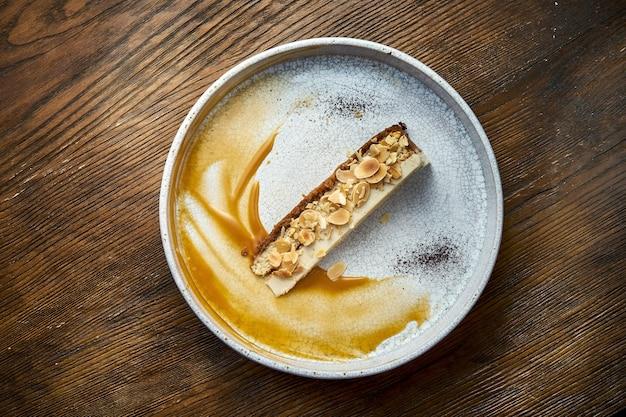 アーモンドとキャラメルソースのチーズケーキのスライス。木製の背景に白いプレートで提供されます。
