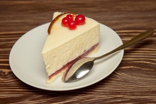 Кусочек чизкейка со свежей красной смородиной на белой тарелке с чайной ложкой на коричневом деревянном фоне. крупным планом вид