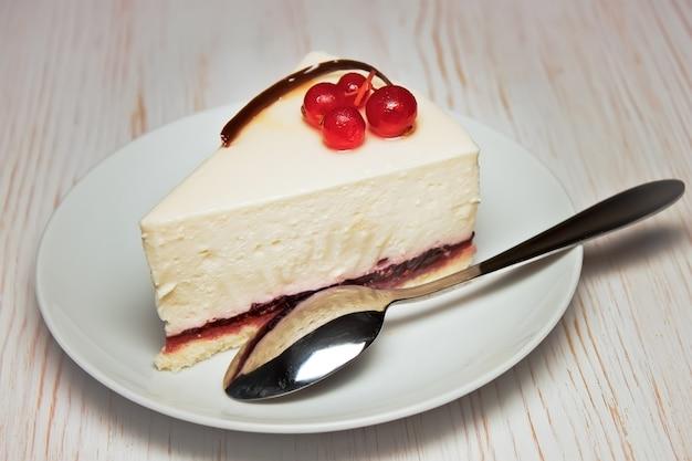 Кусочек чизкейка со свежей красной смородиной на белой тарелке с чайной ложкой на белом деревянном фоне. крупным планом вид