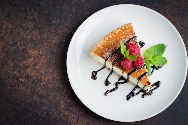 ラズベリーとミントプレート暗い背景のテーブル、上面図、コピースペースにチーズケーキのスライス。