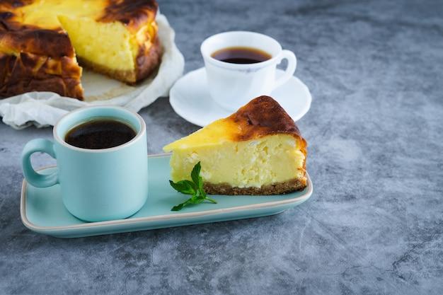 Кусочек чизкейка с двумя чашками кофе.