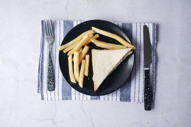 Кусочек куриного сэндвича и чипсов на тарелке, вид сверху