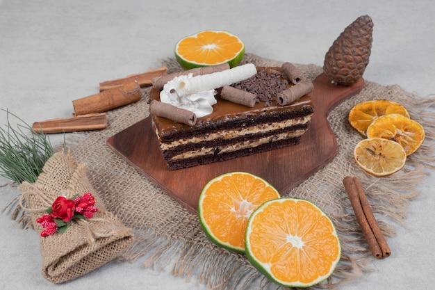 Ломтик шоколадного торта, корицы и кусочки мандарина на мешковине.