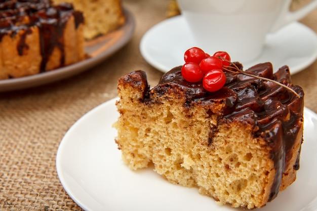 ガマズミ属の木と荒布を着たテーブルの上のコーヒーのカップで飾られたチョコレートケーキのスライス。