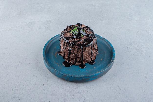 파란색 접시에 시럽으로 장식된 초콜릿 케이크 한 조각. 고품질 사진
